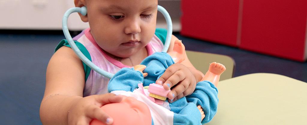 Una pequeña niña jugando al doctor con su muñeca.